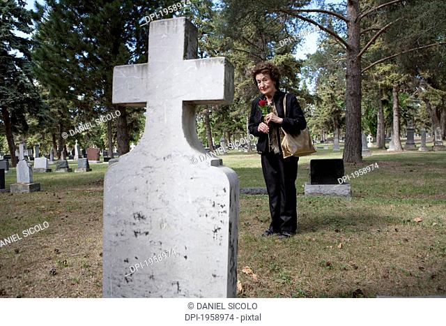 A Woman Visits A Grave In A Cemetery; Edmonton, Alberta, Canada
