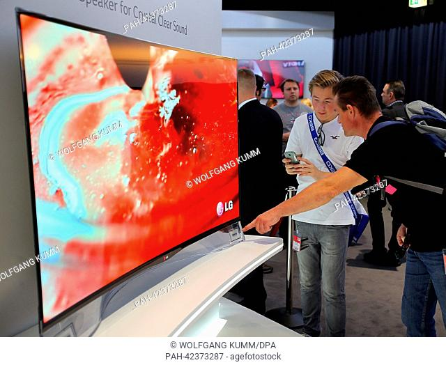 Visitors look at ultra flat, bent TV screens in the halls of the International radio exhibition (Internationale Funkausstellung, IFA) in Berlin, Germany