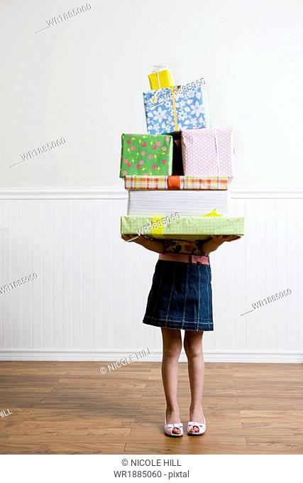 birthday girl carrying a stack of presents