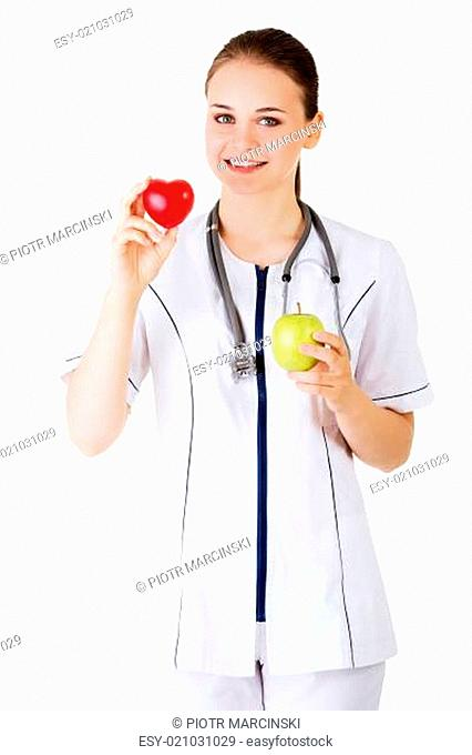 Smiling woman doctor with a green apple and red heart