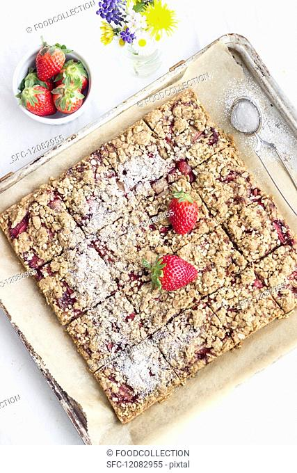 Strawberry crumble slices on a baking tray