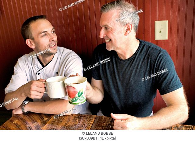 Cafe owner and chef having coffee in restaurant