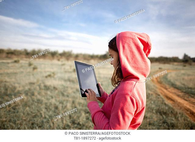 girl in the field with tablet