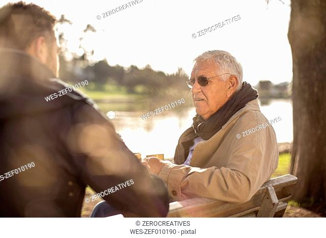 Senior man and adult son sitting on a bench talking