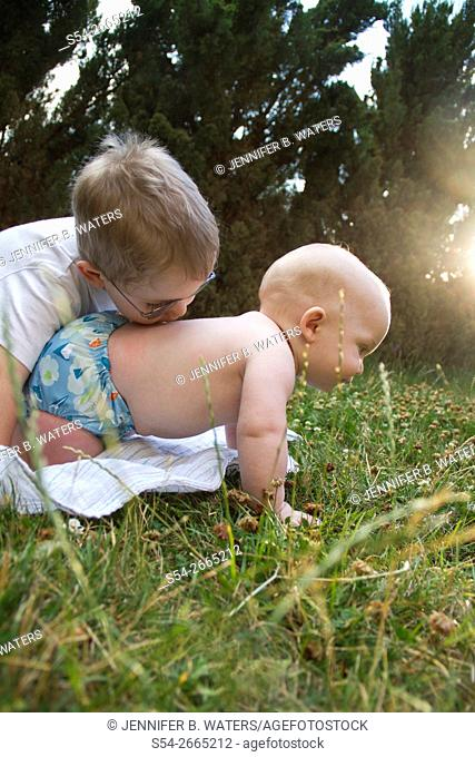 A boy kisses his baby brother's back outdoors