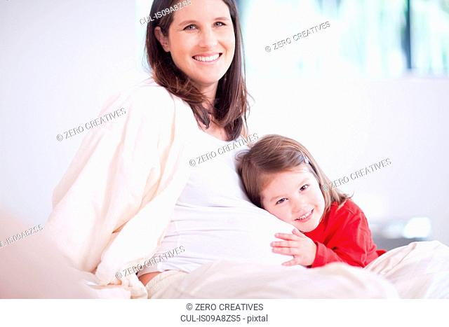 Young daughter hugging mothers bump on bed