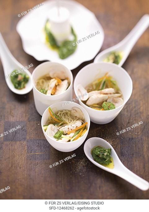 Noodle soup with chicken, vegetables and herb pesto