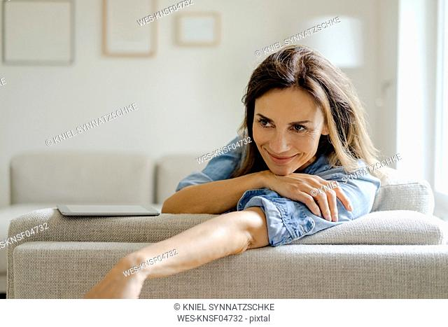 Portrait of smiling mature woman resting on couch at home