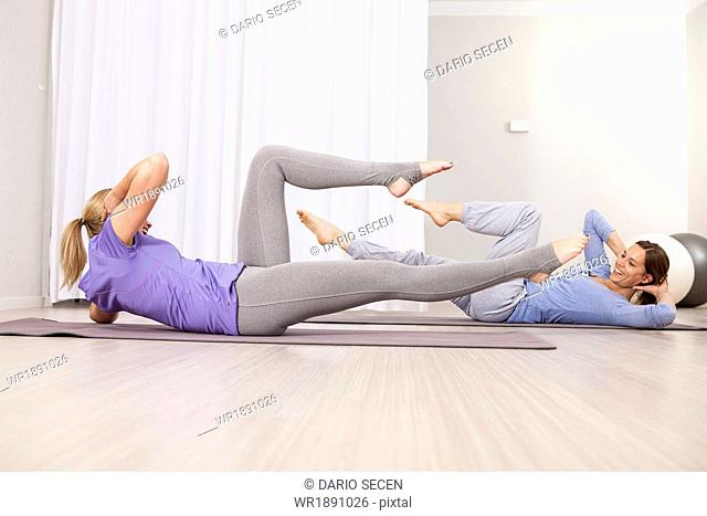 Women doing sit-ups on Pilates class
