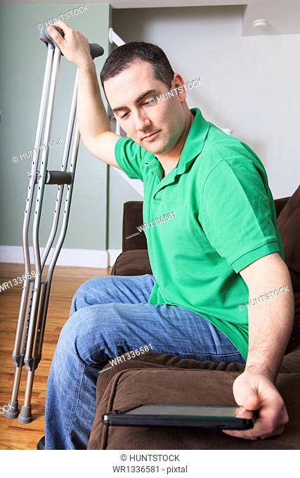 Man after anterior cruciate ligament (ACL) surgery with cane and an digital tablet at home