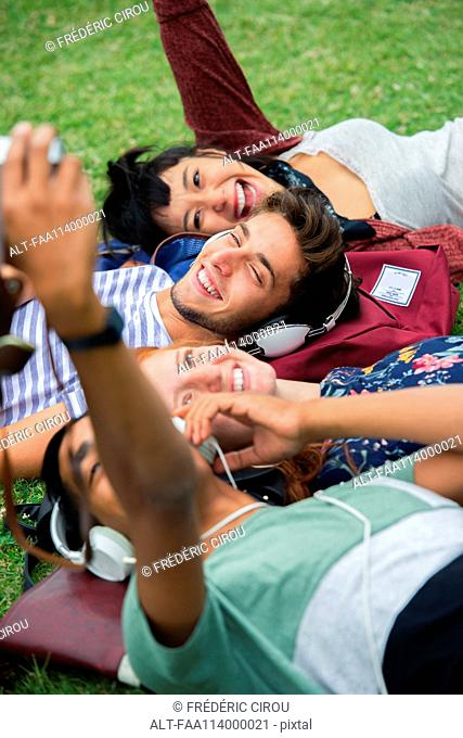 Group of friends posing for a photograph together while lying on grass