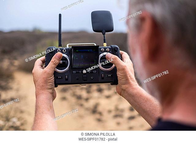 Senior man using telecontrol for drone