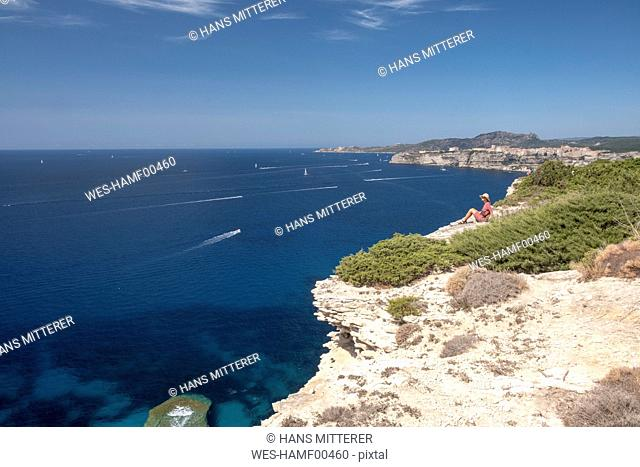 Corsica, Mediterranean coast, woman sitting on rocky cliff