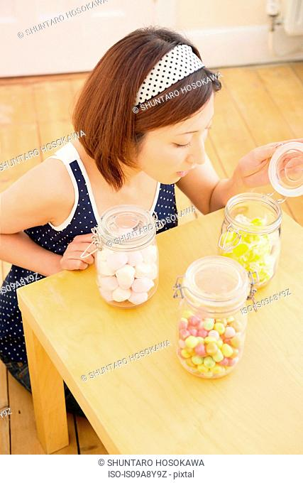 Woman looking into candy jar