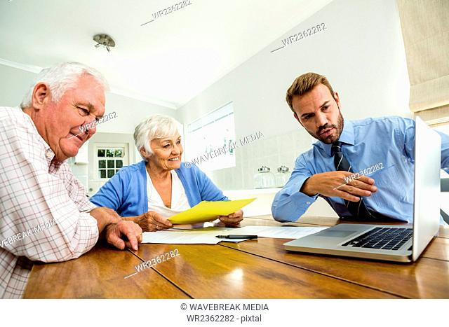 Agent suggesting senior couple on laptop at table