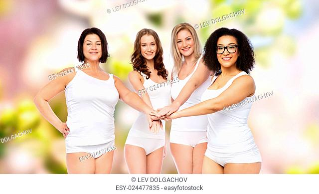 gesture, friendship, beauty, body positive and people concept - group of happy different women in white underwear holding hands together on top over natural...