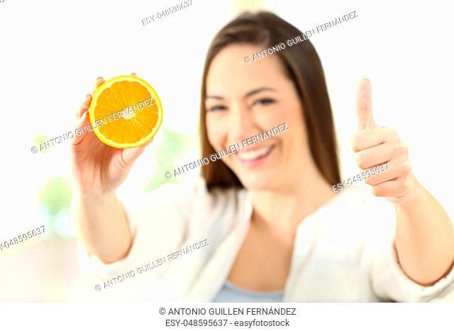 Happy woman showing half orange with thumbs up at home