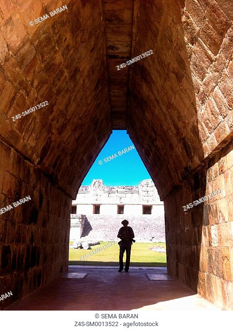 Tourist at the entrance to the Quadrangle Of The Nuns in Uxmal ruins, Prehispanic Mayan city of Uxmal Archaeological Site, Yucatan Province, Mexico