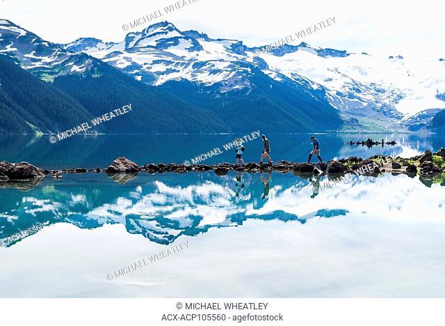 Hikers navigate rock stepping stones at Garibaldi Lake, Garibaldi Provincial Park, British Columbia, Canada