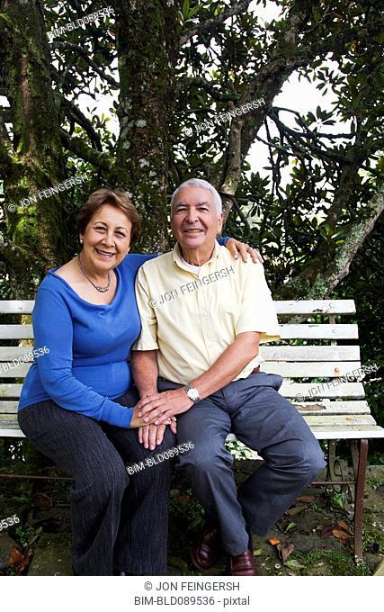 Senior Hispanic couple sitting on park bench