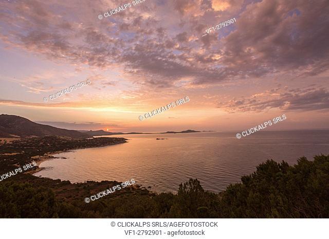 The colors of sunrise are reflected on the sea around the beach of Solanas Villasiumus Cagliari Sardinia Italy Europe