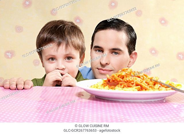 Man and his son with a plate of fettuccine pasta