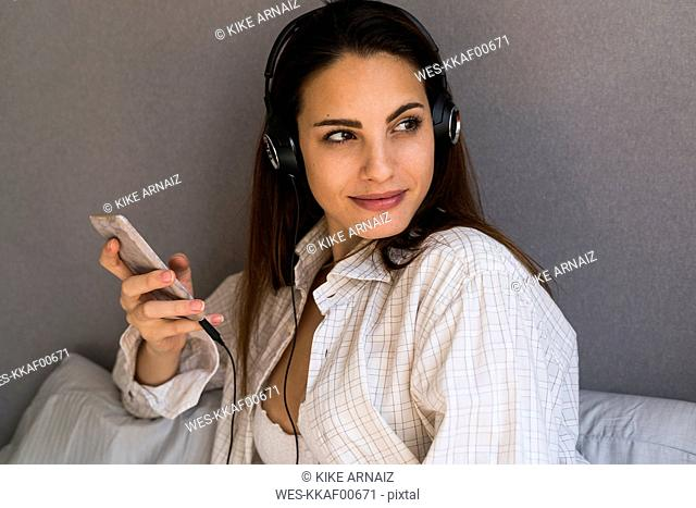 Portrait of smiling young woman with cell phone listening music with headphones at home