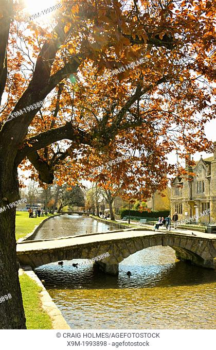 The village of Bourton-on-the-Water, Gloucestershire, England is famous for its picturesque High Street, flanked by long wide greens and the River Windrush