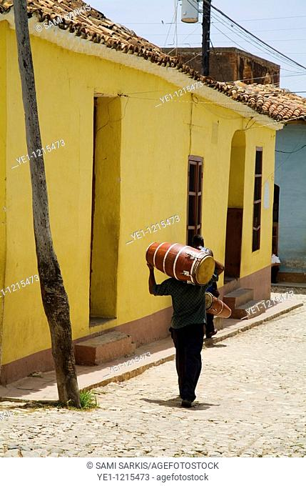 Men carrying drums on their shoulders along a cobblestone street, Trinidad, Cuba