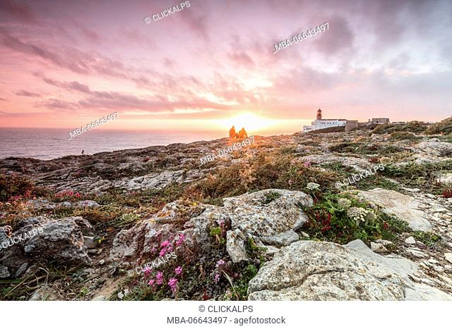 Pink sky at sunset frames the lighthouse overlooking the Atlantic Ocean Cabo De Sao Vicente Sagres Algarve Portugal Europe