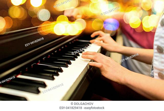 music, musical instruments and people concept - close up of woman hands playing piano over lights background