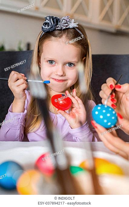 Easter, family, holiday and child concept - close up of little girl and mother coloring eggs for Easter. Cozy home atmosphere. Easter