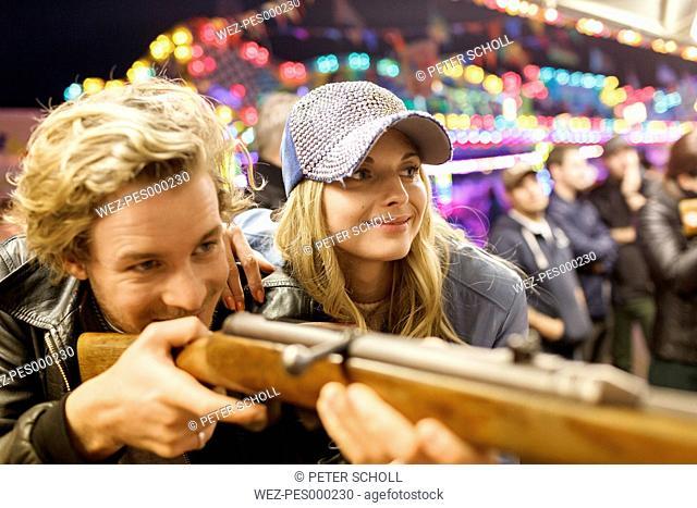 Young couple at fun fair at shooting gallery