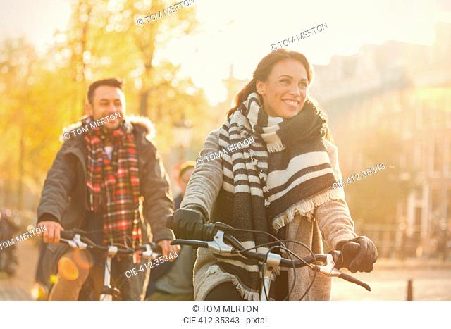 Smiling young couple bike riding on urban autumn street