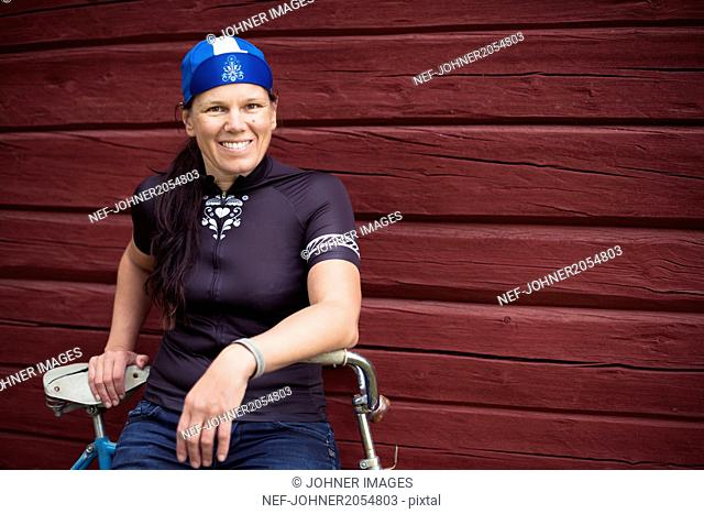 Portrait of mid-adult woman sitting on bicycle