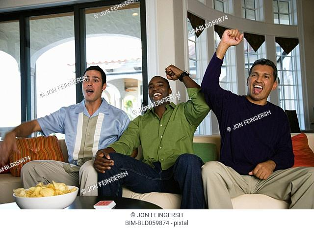 Multi-ethnic men cheering on sofa