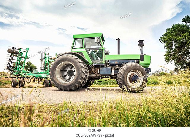 Farmer driving tractor on rural road