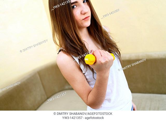 Young woman wearing yellow exercise shirt doing arm curls looking at bicep