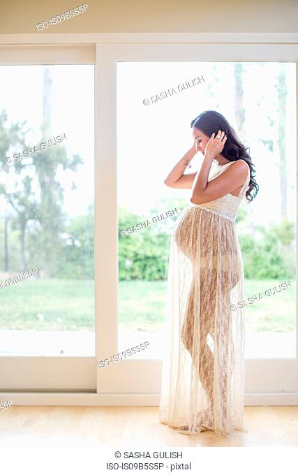 Profile of pregnant woman wearing sheer dress