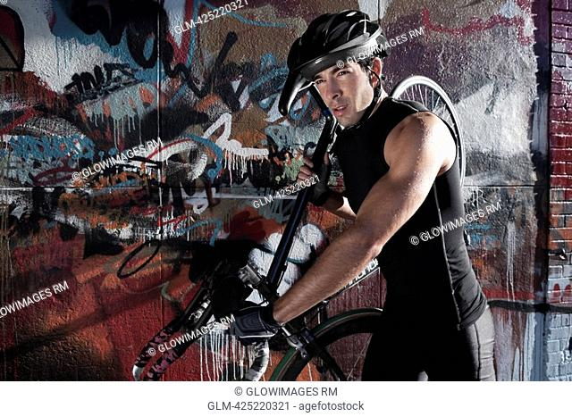 Man carrying a bicycle on his shoulders in front of a graffiti covered wall