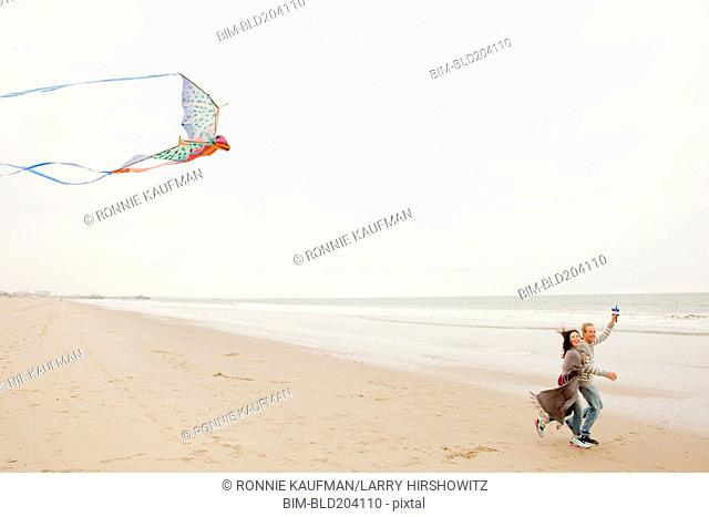 Older Caucasian couple flying kite on beach