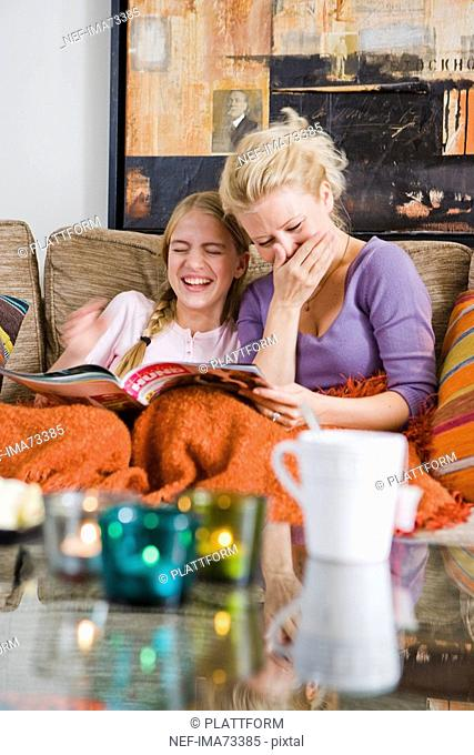 Mother and daughter laughing while reading a weekly, Sweden