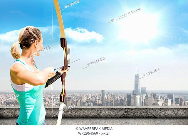 A woman archer is holding a bow and is ready to throw one narrow on cityscape background