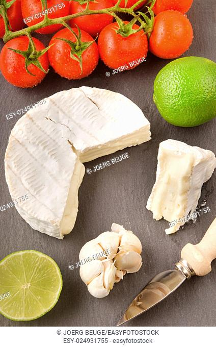 camembert with lime, garlic, tomato and cheese knife on slate