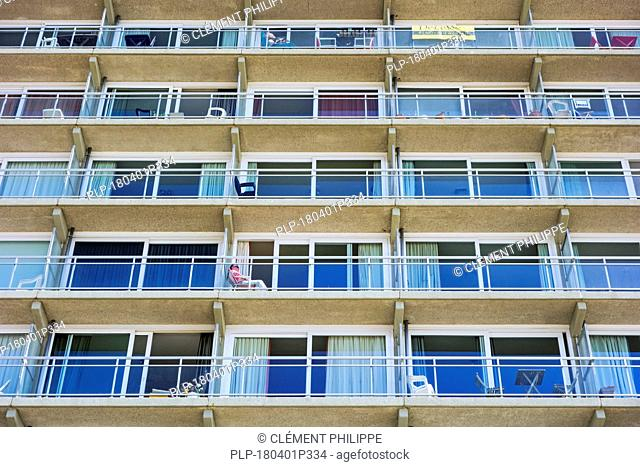 Man resting in chair on balcony of flat in apartment block