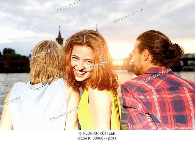 Germany, Berlin, Friend sitting at Spree river, enjoying sunset