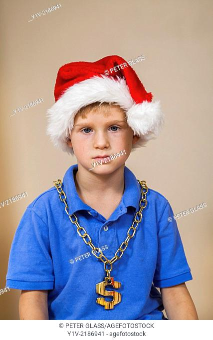 Young boy wearing a Santa hat and a US money symbol chain
