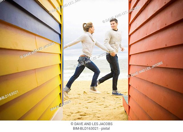 Caucasian couple walking near beach huts