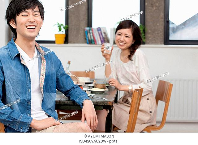 Portrait of young couple enjoying meal at table