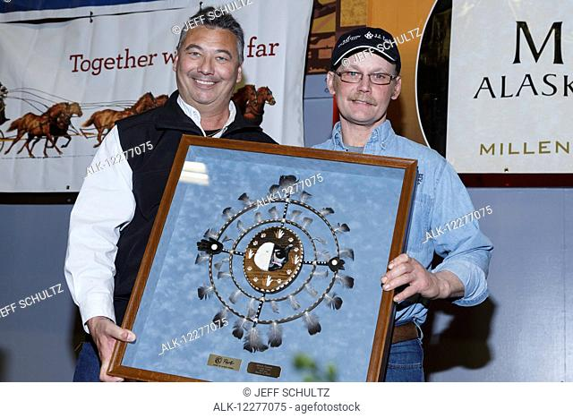 Mitch Seavey (R) receives the PenAir Spirit of Alaska award from Danny Seybert of PenAir at the finishers banquet in Nome during Iditarod 2015